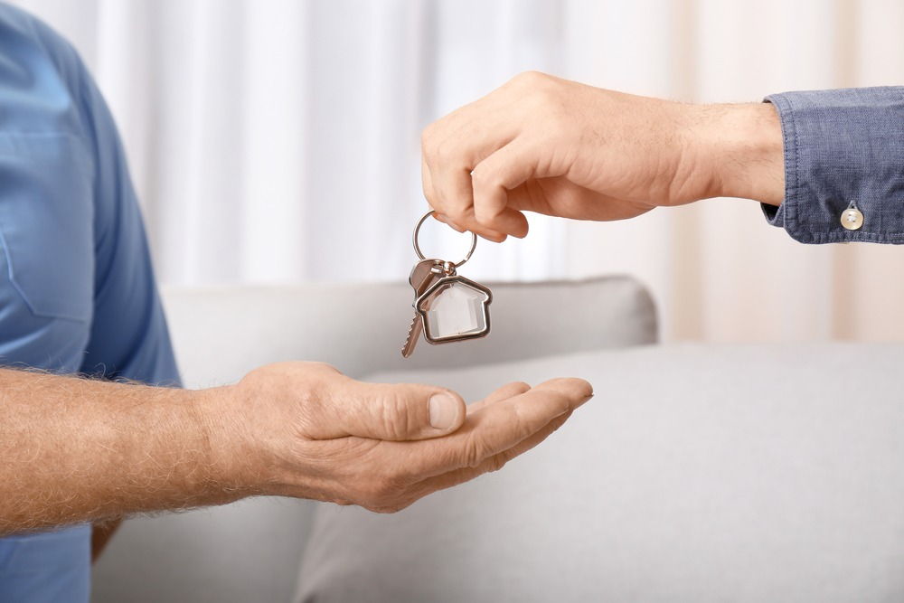 Real estate agent giving house key to senior man indoors